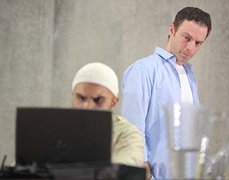 Usman Ally as Bashir and Justin Kirk as Nick, standing behind him, photo by Joan Marcus.