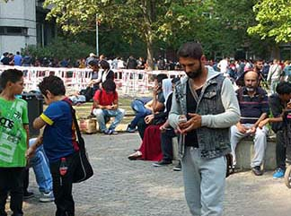 Refugee talking on his cell phone, photo Lucy Komisar.